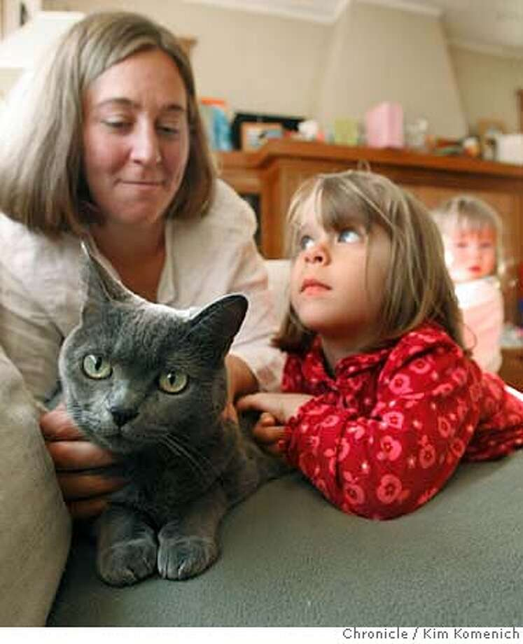 PETFOOD22_019_KK.JPG  Emily Newman of Berkeley, left, and daughter Katie Abramson Newman (cq-no hyphen), 4 hold their cat Louise, a 12-year-old domestic shorthair. Louise has kidney failure and her owners think it's from eating a poisoned batch of cat food. (The vet says it's not). Now Louise has to eat baby food and her owners have to give her an IV syringe every night. (In the background is Katie's sister Erin Abramson Newman, 1.  Photo by Kim Komenich/The Chronicle  **Emily Newman, Katie Abramson Newman, Erin Abramson Newman �2007, San Francisco Chronicle/ Kim Komenich  MANDATORY CREDIT FOR PHOTOG AND SAN FRANCISCO CHRONICLE. NO SALES- MAGS OUT. Photo: Kim Komenich