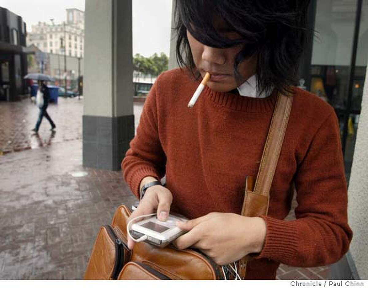 Cal junior Marc Merza adjusts the volume on his iPod in downtown Berkeley, Calif. on Tuesday, March 20, 2007. A spike in iPod thefts around the Bay Area, including several in Berkeley the past few months, has prompted BART officials to post warnings to commuters and police officials to set-up sting operatinos to nab would-be thieves. PAUL CHINN/The Chronicle **Marc Merza Ran on: 03-21-2007 Ena Ladi listens to her iPod at BARTs Downtown Berkeley Station. She says she doesnt worry about being robbed. Ran on: 03-21-2007 Ena Ladi listens to her iPod at BARTs Downtown Berkeley Station. She says she doesnt worry about being robbed.