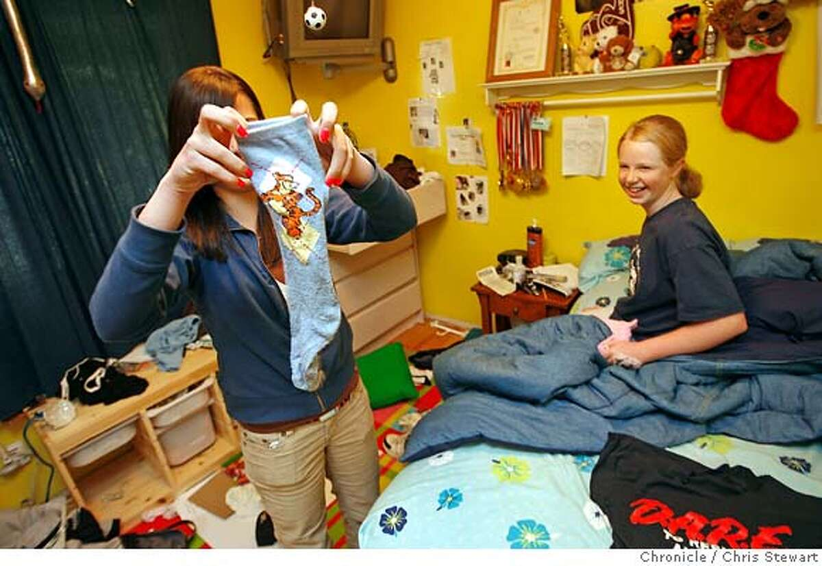 """Eighth grader T. K. Scott (cq), 14, holds up a Tigger sock to the amusement of her younger sister, sixth grader Sydni Scott (cq), 11. Both have been """"dress coded"""" at Redwood Middle School in Napa for wearing non school-approved fashions. The Tigger sock is prohibited. Photographed today, March 20, 2007 in their Napa home. Mother Donnell Scott (cq) and their attorney Sharon L. O'Grady (cq) (both not pictured) consider the school dress code policy """"inconsistent and inconsistently enforced."""" Chris Stewart / The Chronicle Napa, dress code, T. K. Scott, Sydni Scott, Donnell Scott, Sharon L. O'Grady"""