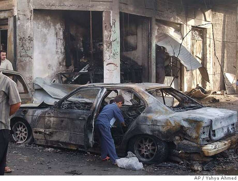 ** CORRECTS TO BURNED OUT CAR ** An Iraqi child looks through the wreck of a car at the scene of a bombing in Tuz Khormato, 210 kilometers (130 miles) north of Baghdad Friday Sept. 16 2005. In the Friday mosque attack, a suicide car bomber detonated his vehicle as worshippers left the Hussainiyat al-Rasoul al-Azam mosque in Tuz Khormato, said police Col. Sarhat Qader.(AP Photo/Yahya Ahmed) Ran on: 09-17-2005  An Iraqi child looks through the wreck of a car at the scene of a bombing in Tuz Khormato. Photo: YAHYA AHMED