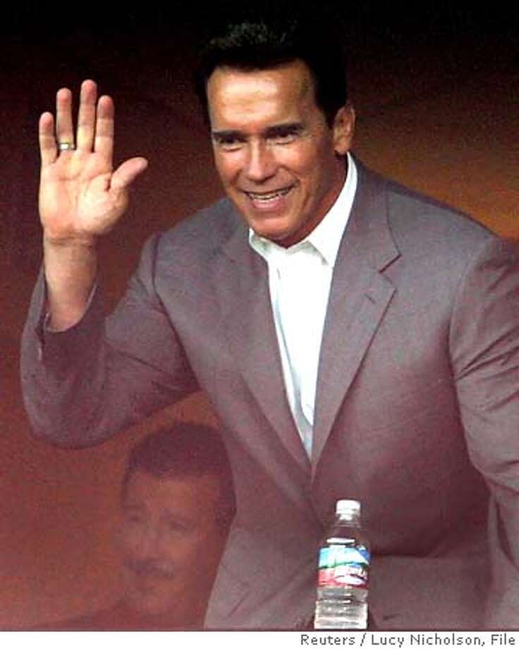 California Governor Schwarzenegger (R) waves to the crowd as he watches the game between the Oakland Athletics and the Los Angeles Angels with Los Angeles Angels owner Arte Moreno (L) in Anaheim, California, August 30, 2005. A group of nurses, teachers and firefighters took over part of Angel Stadium to demonstrate against Schwarzenegger's November 8 special election. REUTERS/Lucy Nicholson 0 Photo: LUCY NICHOLSON