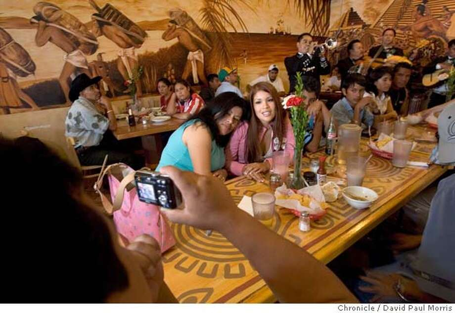 OAKLAND, CA. AUGUST 2005: Ruben Ramierz takes a photo of Rosa Robles and her daughter Caroline Robles in El Huarache Azteca in Oakland, California. They come all the way from Fairfield, CA for the authentic Mexican food. Photo by David Paul Morris the Chronicle Photo: David Paul Morris