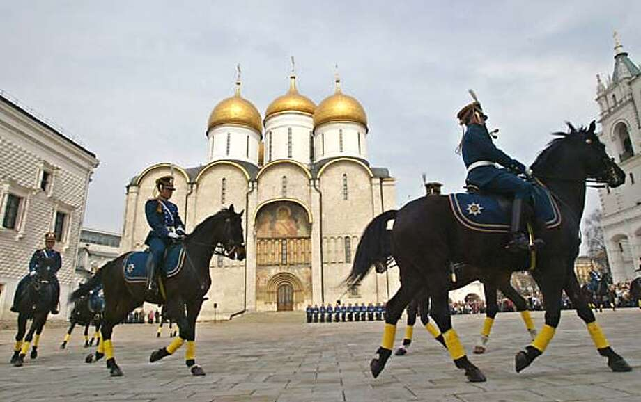 Kremlin cavalry guards ride around Cathedral Square during a ceremony of the Changing of the Guard in front of the Assumption Cathedral in the Kremlin in Moscow, Saturday, April 16, 2005. The Kremlin inaugurated a new czarist-style ceremony of the Changing of the Guard which it hopes will pull in tourists like the goose-stepping Soviet guards outside Lenin's Mausoleum did during the communist era. The Kremlin guards were wearing uniforms designed to resemble Russian military uniforms used at the time of Czar Nicholas II in 1907-1913. (AP Photo/Alexandre Korolkov, Izvestia) ** RUSSIA OUT ** Photo: ALEXANDRE KOROLKOV