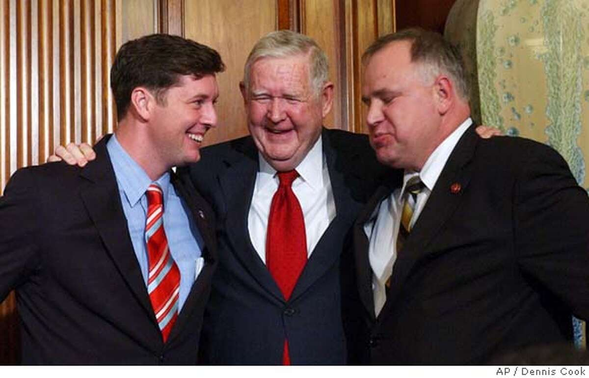 Rep. John Murtha, D-Pa., center, celebrates with Rep. Patrick Murphy, D-Pa., left, Rep. John Murtha, D-Pa., and Rep. Tim Walz, D-Minn. on Capitol Hill in Washington, Friday, March 23, 2007, after a sharply divided House of Representatives voted to order President Bush to bring combat troops home from Iraq next year. Both Murphy and Walz are Iraq War veterans. (AP Photo/Dennis Cook)