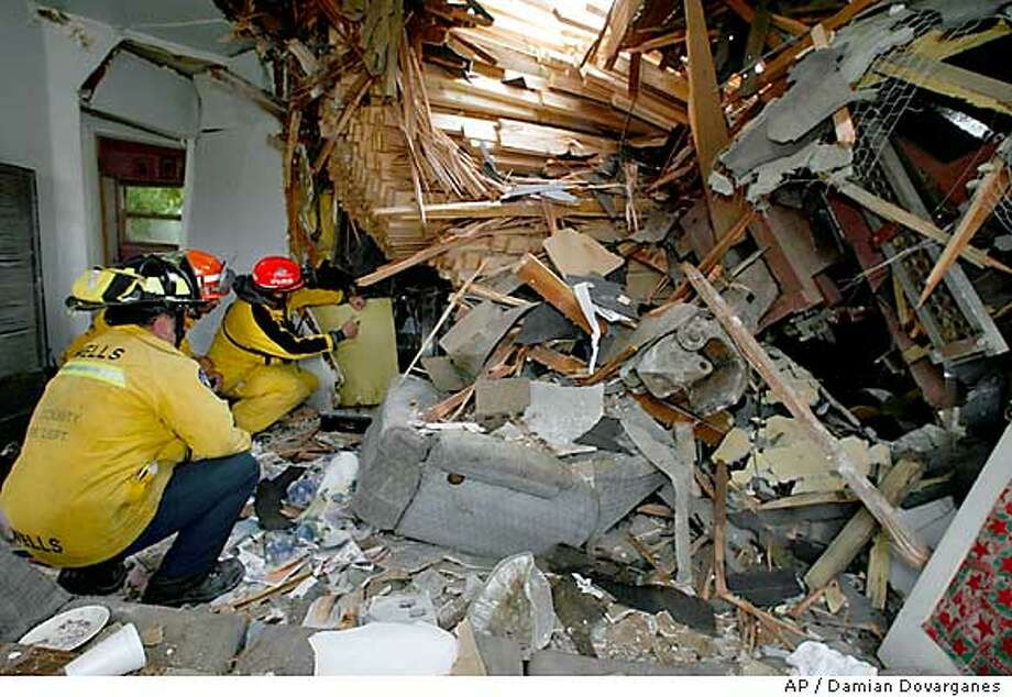 Members of Los Angeles County Fire Urban Search and Rescue Task Force 103 look Saturday, June 21, 2003, inside a home damaged when a freight train derailed Friday in Commerce, Calif. Residents and officials on Saturday challenged a decision by railroad officials to divert two dozen runaway freight cars onto a side track in Commerce without warning, causing them to and destroy or damage four trackside homes and scatter tons of lumber like matchsticks. (AP Photo/Damian Dovarganes) Photo: DAMIAN DOVARGANES