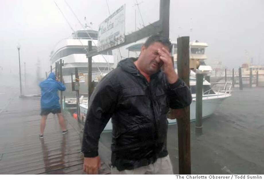 "Rocky Stone, foreground, fights the stinging rain as he and Mark Powell, left, struggle to secure rocking fishing boats in a harbor at Carolina Beach, N.C., Wednesday, Sept. 14, 2005, as Hurricane Ophelia pounds the coast. Stone said of the lingering hurricane, ""If this is a category 1, I don't want to see a 3 or a 4."" (AP Photo/The Charlotte Observer, Todd Sumlin) Photo: TODD SUMLIN"