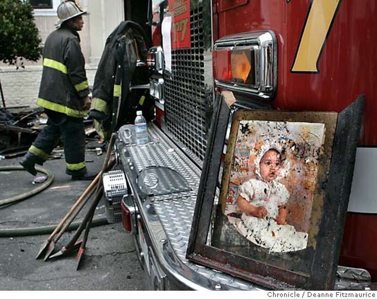 A firefighter found this photo of a baby one of the burned out units. Firefighters are on the scene after an early morning fire on Capp Street in the Mission District. Deanne Fitzmaurice / San Francisco Chronicle