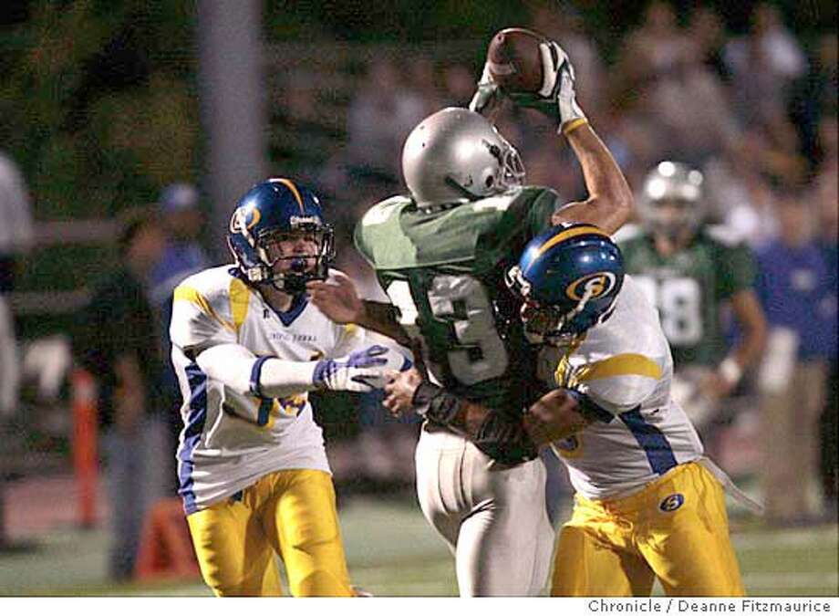 Vincent Colvis pulls in a long pass to set up a touchdown in the first quarter. ( left) Max Treub and Edward Berry on defense. Serra High School vs De La Salle High School football at De La Salle in Concord.  Deanne Fitzmaurice / San Francisco Chronicle Photo: Deanne Fitzmaurice