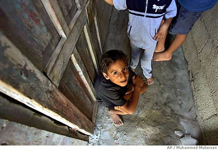A Palestinian boy waits by the door for relatives he never saw during Israel's occupation of Gaza, in the Mawasi area in the Gaza Strip, Tuesday, Sept. 13, 2005 . For more than four years, the families of Mawasi have been effectively cut off from their relatives in the nearby Gaza town of Khan Younis, trapped behind a security fence that protected the Gush Katif bloc of settlements in Gaza. (AP Photo/Muhammed Muheisen) Photo: MUHAMMED MUHEISEN