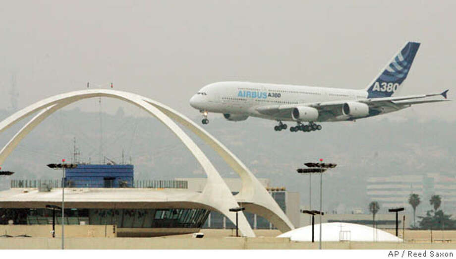 An Airbus A380, the world's largest passenger jet, passes the Los Angeles International Airport Theme building as it prepares to touch down on the inaugural visit of the superjumbo jet to Los Angeles, Monday, March 19, 2007. (AP Photo/Reed Saxon) Photo: Reed Saxon