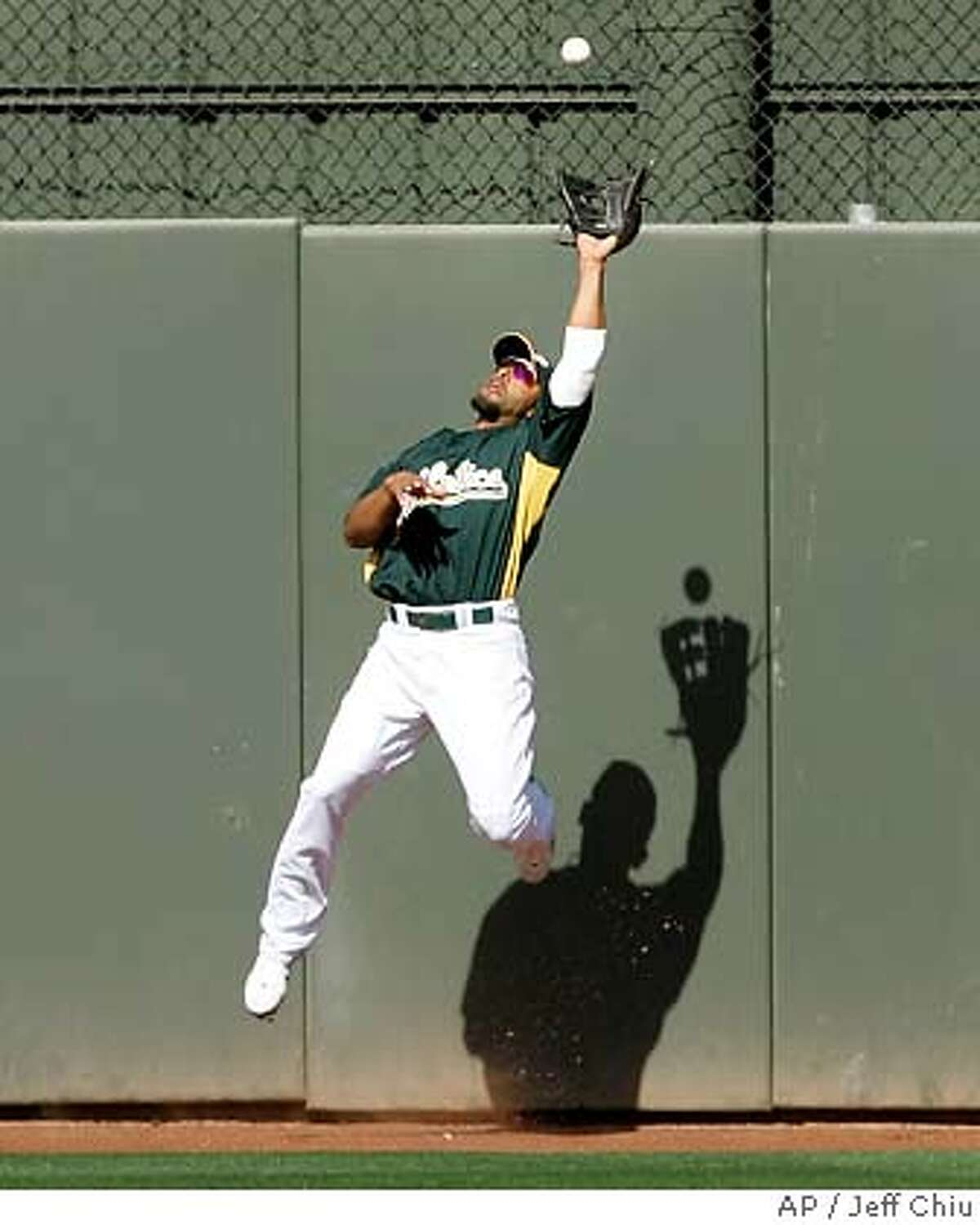 Oakland Athletics' Hiram Bocachica catches a fly ball hit by Chicago White Sox's Juan Uribe in the seventh inning of a spring training baseball game in Phoenix, Tuesday, March 20, 2007. (AP Photo/Jeff Chiu)