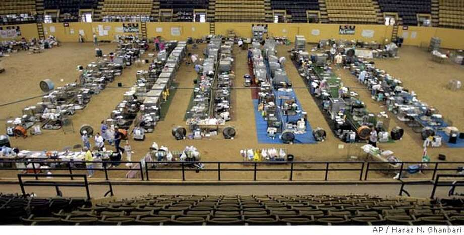 Rows of cages temporarily housing small dogs spread out across the floor, Wednesday, Sept. 14, 2005, in the Hurricane Katrina Emergency Animal Shelter at Louisiana State University's John M. Parker Coliseum in Baton Rouge, La. As of Wednesday, the shelter was housing over 1,000 companion animals, including 641 dogs, 391 cats, and assorted pigs, rabbits, guinea pigs, ferrets, hamsters, gerbils, mice, tortoises, and birds. Since the shelter opened during the days following the hurricane, almost 300 pets have already been reunited with their owners although the number of admissions is still surpassing the number of discharged animals. (AP Photo/Haraz N. Ghanbari) THIRD OF SEVEN STAND ALONE IMAGES Photo: HARAZ N. GHANBARI