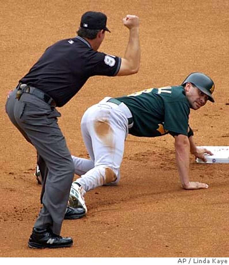 Oakland Athletics' Jason Kendall, right, reaches for second base as umpire Paul Nauert, left, calls hiim out after Kendall was thrown out trying to reach on a single to right in the first inning against the Texas Rangers, Sunday, Sept. 11, 2005, in Arlington, Texas. (AP Photo/Linda Kaye) Photo: LINDA KAYE