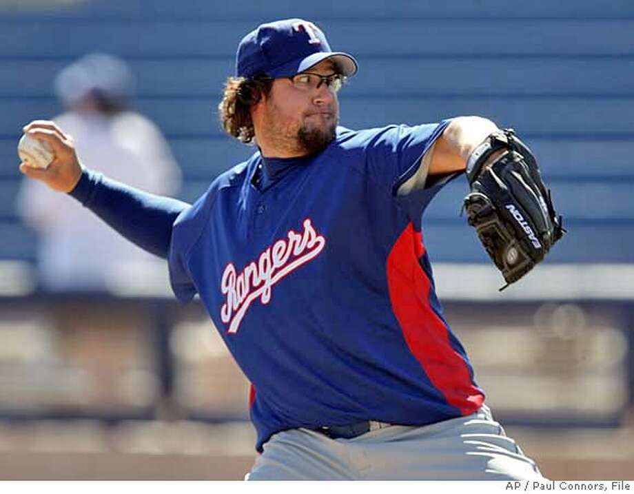 """Texas Rangers' Eric Gagne delivers a pitch from the mound as he faces the Milwaukee Brewers in a spring training """"B"""" baseball game Monday, March 12, 2007, in Phoenix.(AP Photo/Paul Connors) Photo: Paul Connors"""