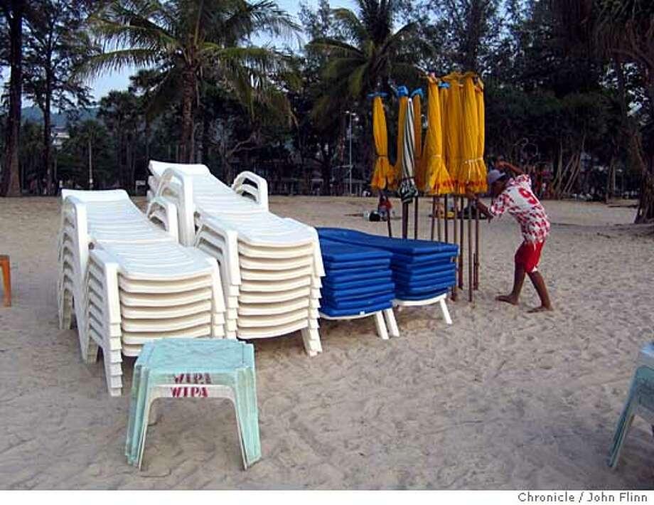 TRAVEL THAILAND -- With little business, a vendor packs up beach chairs and umbrellas early on Patong Beach, Phuket Island, Thailand. Ran on: 09-15-2005  With few customers, a vendor on Patong Beach on Thailand's Phuket Island packs up beach chairs and umbrellas . Photo: John Flinn
