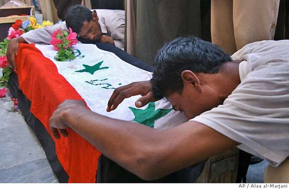 Relatives grieve over the casket of Fawaz Yahya, 23, in the Holy Shiite city of Najaf, Thursday, Sept. 15, 2005. Fawaz Yahya was killed the previous day in Baghdad car bomb explosion.(AP Photo/Alaa al-Marjani) Photo: ALAA AL-MARJANI