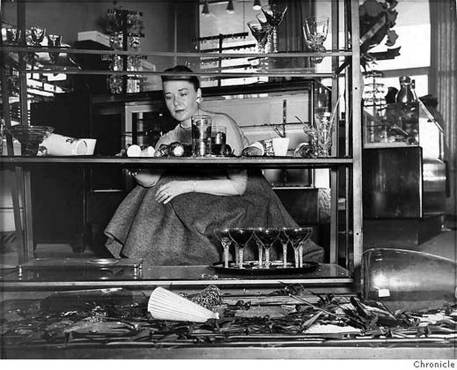 Margaret Gaines began to tidy up the debris of broken glassware at a Stonestown shop following the earthquake in March 1957 Photo: Chronicle File Photo 1957