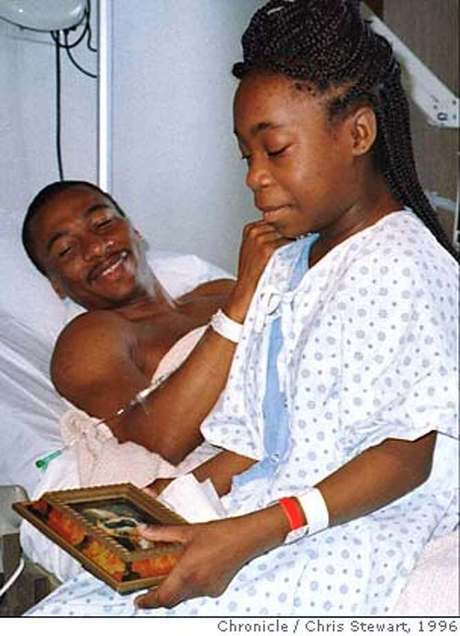 FILE--Renada Daniel-Patterson shows a picture of her pet dog to her father and inmate David Patterson shortly before he donated a kidney to her in San Francisco in this March 12, 1996 file photo. Now the transplanted kidney is failing, and David Patterson, who has more than three years remaining on his burglary and drug convictions, wants to give the teen-ager another chance by donating his remaining kidney. (AP Photo/San Francisco Chronicle, Chris Stewart) ALSO RANF: 1//19/99W CAT Photo: CHRIS STEWART