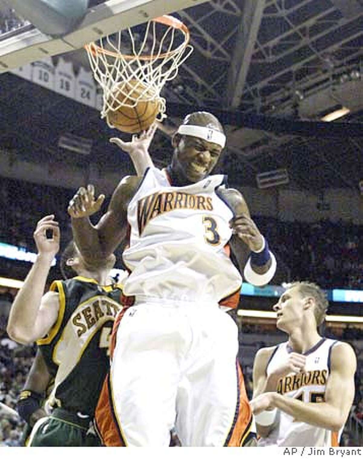 Golden State Warriors' Al Harrington (3) celebrates a basket against the Seattle SuperSonics during the first half of an NBA basketball game Saturday, March 17, 2007 in Seattle. Defending for the Sonics' is Nick Collison, left; Warriors' Andris Biedrins, right, of Latvia, is at right. (AP Photo/Jim Bryant)
