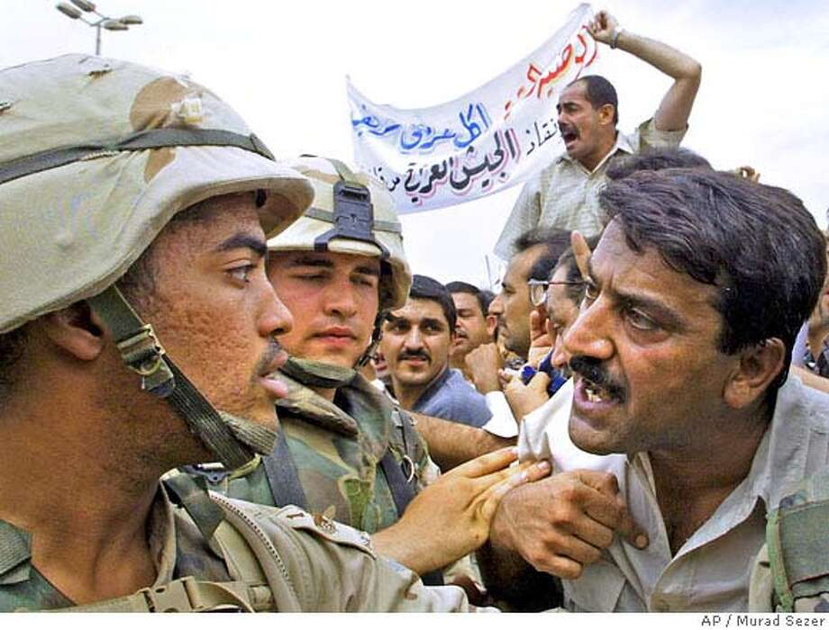 A former Iraqi Army soldier argues with a U.S. soldiers during a protest outside of the Republican Palace in Baghdad on Monday, June 2, 2003. Hundreds of former Iraqi soldiers protested outside the office compound of Iraq's U.S. occupiers, demanding pay for all troops dismissed when the American civil administrator abolished the country's military. The protest was largely peaceful, though there were a few scuffles between demonstrators and American soldiers guarding the entrance to the compound, which until the U.S. invasion was a palace compound of Saddam Hussein and his top officials. (AP Photo/Murad Sezer) Photo: MURAD SEZER