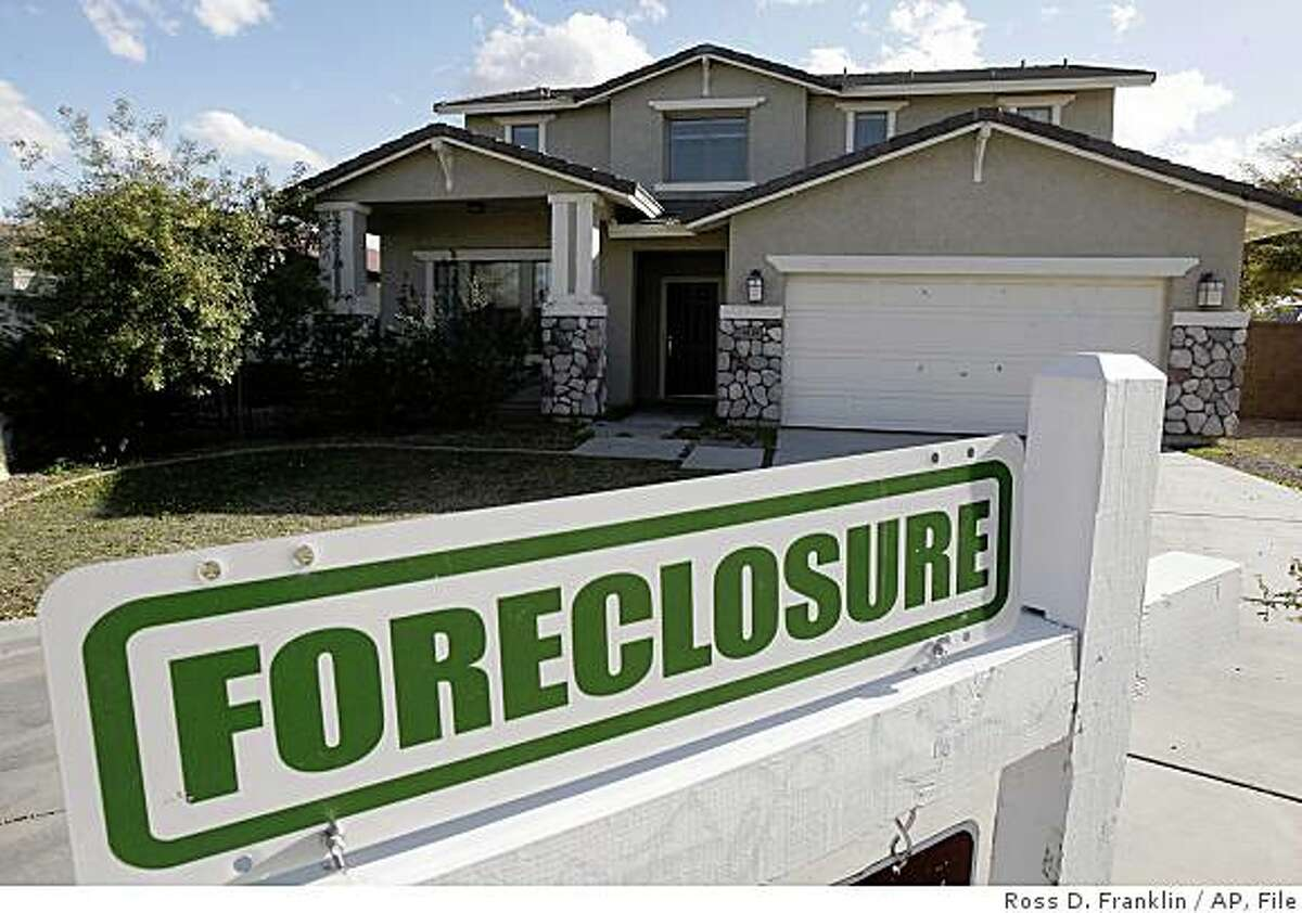 FILE - In this Feb. 17, 2009 file photo, a foreclosure sign sits outside a home for sale in Phoenix. Arizona has one of the highest foreclosure rates in the country.