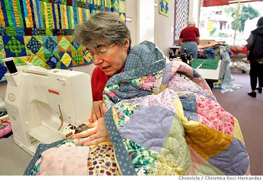 CHRISTINA KOCI HERNANDEZ/CHRONICLE Quilter, Jan Fischer, works diligently to finish quilts.After watching the disaster from Hurricane Katrina unfold, members of the East Bay Heritage Quilters got organized and began making quilts, hundreds of them, to send to katrina victims. One beehive of activity is New Pieces, a fabric store on solano Avenue, where quilters are gathering to cut and sew quilts, to be sent on to Houston. It's just tip of ice berg, say the quilters as the call for more quilts went nationwide to guilting guilds across the country. Photo: CHRISTINA KOCI HERNANDEZ