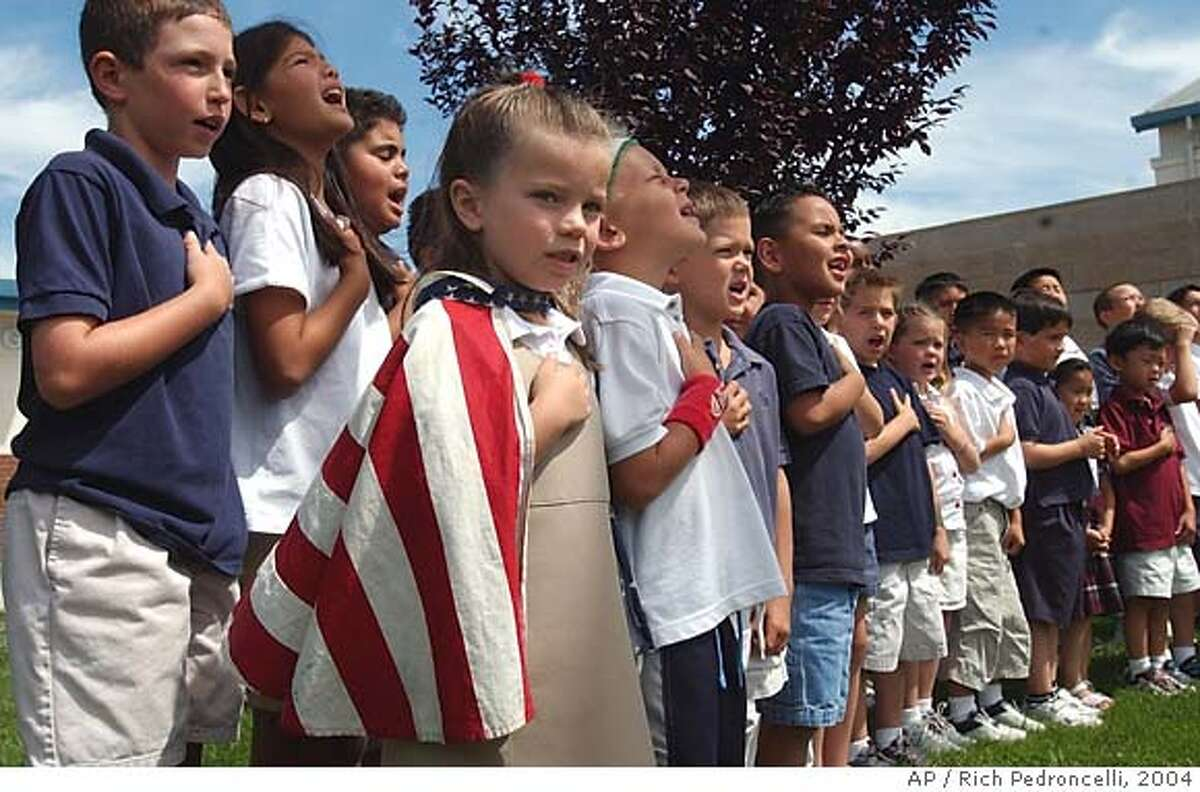 Wearing a cape of the United States flag, kindergartner Natalie Stoecklein, 5, joined other students of the Stone Lake Elementary School, in the Elk Grove Unified School District, in saying the Pledge of Allegiance, Monday June 14, 2004, in Elk Grove, Calif. Earlier in the day the U.S. Supreme Court preserved the phrase
