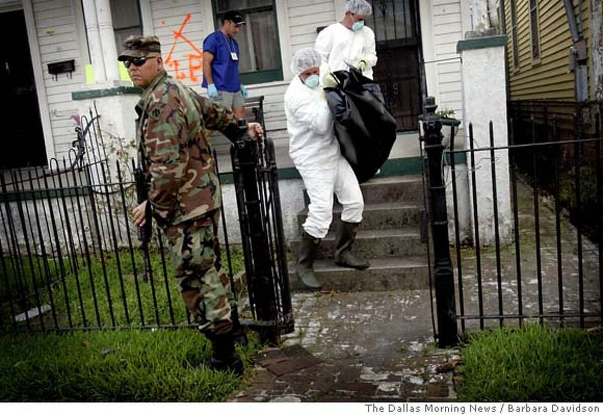 After Hurricane Katrina, An Oklahoma national Guardsman assists workers from a FEMA contractor remove a body of a porch bench Monday, Sept. 12, 2005, in New Orleans. (AP Photo/The Dallas Morning News, Barbara Davidson) ** MANDATORY CREDIT: , MAGS OUT, TV OUT, INTERNET: AP MEMBERS ONLY ** MANDATORY CREDIT: , MAGS OUT, TV OUT, INTERNET: AP MEMBERS ONLY