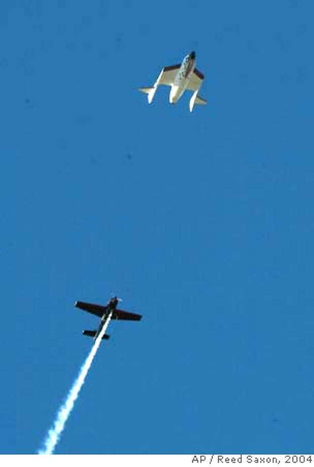 Followed by a chase plane trailing smoke, SpaceShipOne with pilot Brian Binnie at the controls glides back to earth after soaring into space in its quest to win the Ansari X Prize at Mojave, Calif., Airport, Monday, Oct. 4, 2004. (AP Photo/Reed Saxon) Ran on: 10-05-2004  The spaceship: Escorted by a chase plane trailing smoke, SpaceShipOne glides back to earth after claiming the prize. Ran on: 10-05-2004  The spaceship: Escorted by a chase plane trailing smoke, SpaceShipOne glides back to earth after claiming the prize. Ran on: 10-10-2004 Photo: REED SAXON