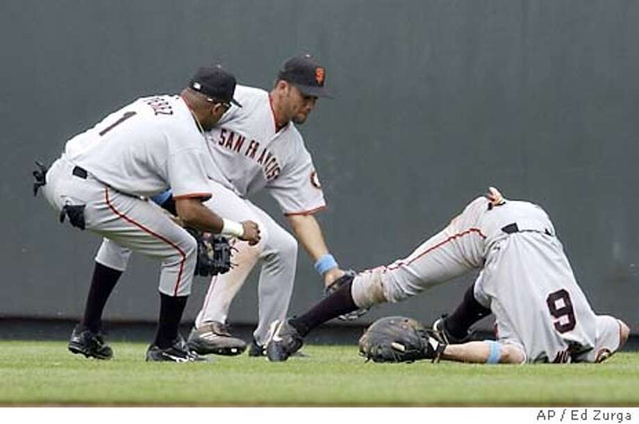 San Francisco Giants first baseman J.T. Snow, right, tumbles to the ground as he, Neifi Perez (1) and Jose Cruz Jr. try to field a ball hit by Kansas City Royals' Angel Berroa in the ninth inning Sunday, June 15, 2003, in Kansas City, Mo. Berroa piced up a double on the play and would score on Mike Sweeney game-winning two-run single. Kansas City won the game 5-4. (AP Photo/Ed Zurga) Photo: ED ZURGA
