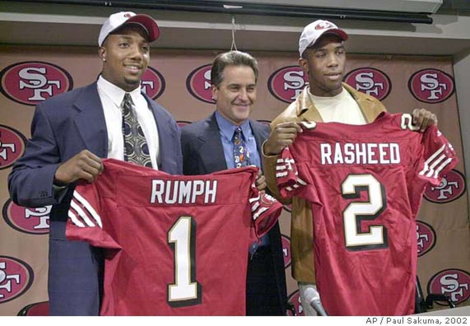 San Francisco 49ers top draft picks Mike Rumph, left, a cornerback from Miami, and Saleem Rasheed, right, a linebacker from Alabama, pose with 49ers coach Steve Mariucci during a news conference in Santa Clara, Calif., Sunday, April 21, 2002. (AP Photo/Paul Sakuma) ALSO RAN 07/24/02 Ran on: 09-30-2004  Mike Rumph's return to right corner should improve the 49ers' play in the secondary. Ran on: 09-30-2004  Mike Rumph's return to right corner should improve the 49ers' play in the secondary. Ran on: 09-30-2004  Mike Rumph's return to right corner should improve the 49ers' play in the secondary. CAT DIGITAL IMAGE Photo: PAUL SAKUMA