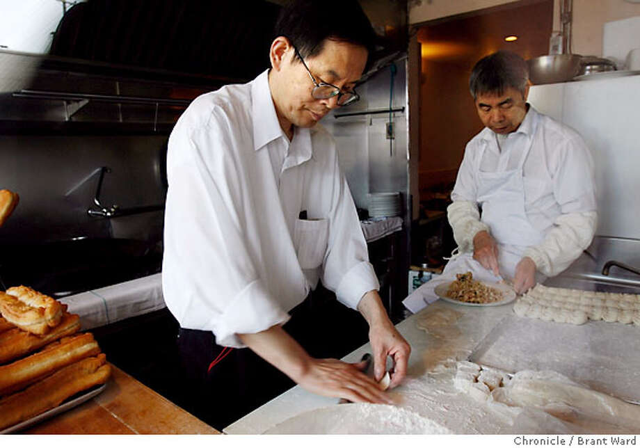 special18001.JPG  The dumplings at the Taiwan Restaurant on Clement Street in San Francisco are something to behold. Chef Michael Wu, left, works on a pan of pot stickers while baker Wong Chen, in the background, prepares the filling. Photographed through the window on Clement Street where patrons can watch the bakers work.  {Brant Ward/San Francisco Chronicle}3/6/07 Photo: Brant Ward