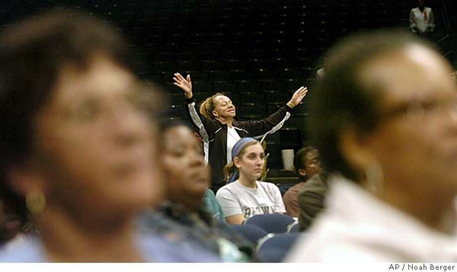 Frankie Williams lifts her hands in prayer during the Oakland United in Love fundraiser for Hurricane Katrina victims on Saturday, Sept. 10, 2005, in Oakland, Calif. The ecumenical event drew about a thousand worshippers and featured singing, prayer and speeches by New Orleans evacuees. (AP Photo/Noah Berger) Photo: NOAH BERGER