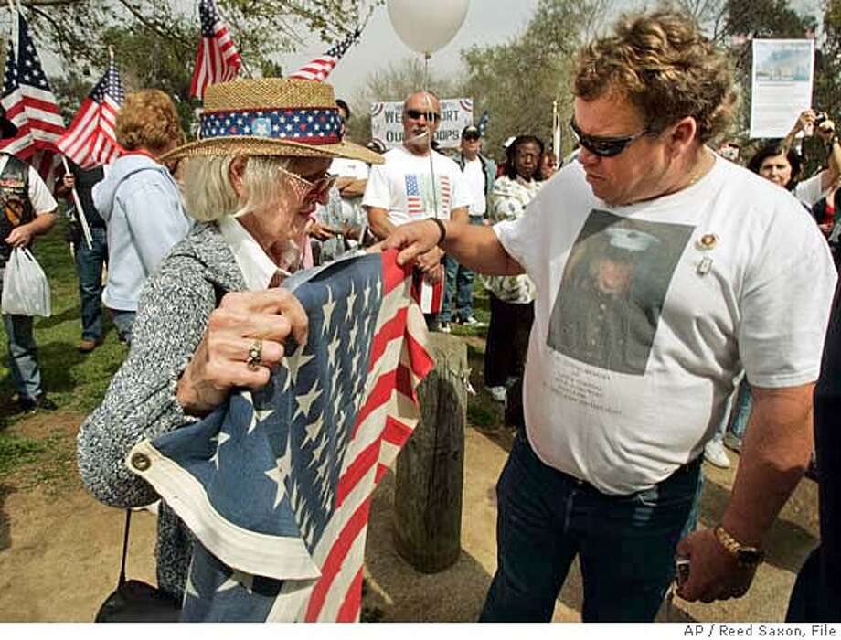 "Jeanne Hamley, left, whose brother died in World War II, shows the flag presented to her Gold Star mother to Mark Crowley, whose son was killed in Iraq, at a rally sponsored by Move America Forward in Los Angeles, Friday, March 9, 2007. Crowley's Marine son Kyle was killed in Ramadi in 2004 at the age of 18. Friday's rally was one stop on a caravan tour called ""These Colors Don't Run,"" traveling from San Francisco to Washington, D.C., for a rally on March 17. Hamley presented her mother's flag to Crowley to accompany the group to Washington. (AP Photo/Reed Saxon) Photo: Reed Saxon"