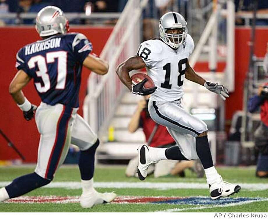 Oakland Raiders wide receiver Randy Moss (18) breaks away from the defensive efforts of New England Patriots' Rodney Harrison to score a 73-yard touchdown in the second quarter in Foxborough, Mass., Thursday, Sept. 8, 2005. (AP Photo/Charles Krupa) Photo: CHARLES KRUPA