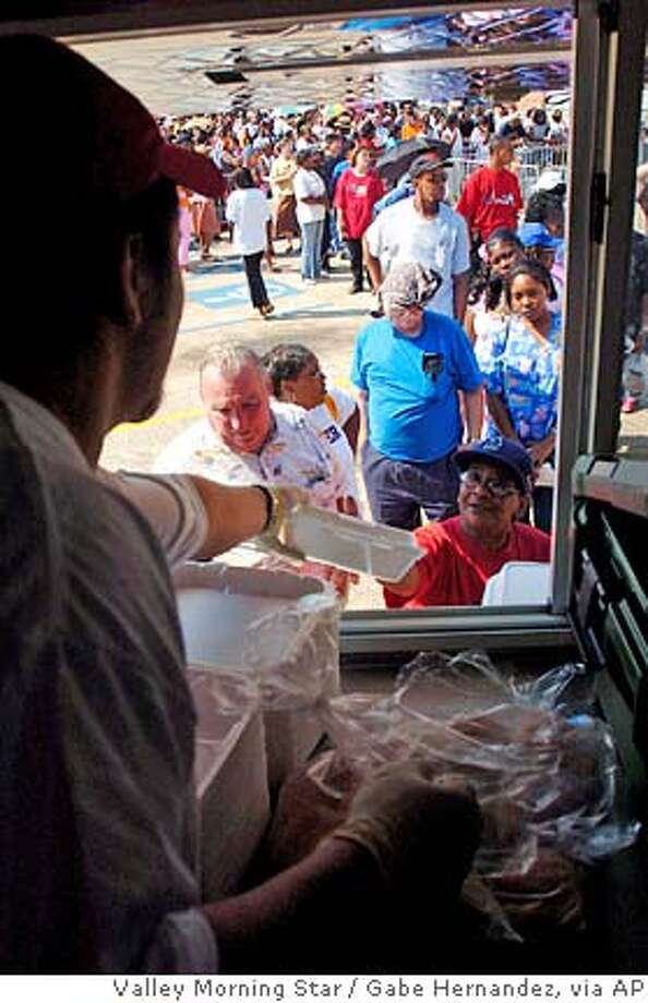 Evacuees from New Orleans, LA stand in line while food was provided by the Salvation Army, as they wait outside of the the East Baton Rouge Office of Family Support Tuesday Sept. 6, 2005 in Baton Rouge, LA. (AP/Gabe Hernandez, Valley Morning Star) Photo: GH
