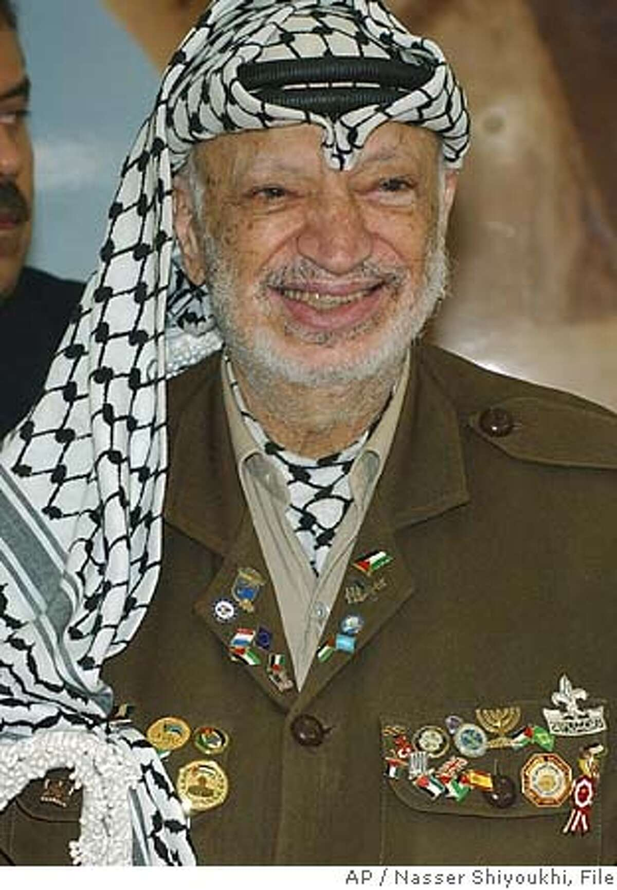 ** FILE ** Palestinian leader Yasser Arafat smiles during a gathering with supporters at his headquarters in the West Bank town of Ramallah, in this Tuesday Aug. 3, 2004 photo. Yasser Arafat's medical records do not give conclusive results as to what caused his death, The New York Times and the Haaretz newspapers reported Thursday. A stroke was the final blow that killed Arafat, but it is not clear what led to a deterioration in his health, The New York Times concluded in its report. The records show that Arafat's symptoms make it highly unlikely that he died of AIDS or poisoning, the newspaper said. Arafat died in a Paris hospital Nov. 11 at the age of 75. He had fallen ill in mid-October, and doctors originally said he had the flu. (AP Photo/Nasser Shiyoukhi)