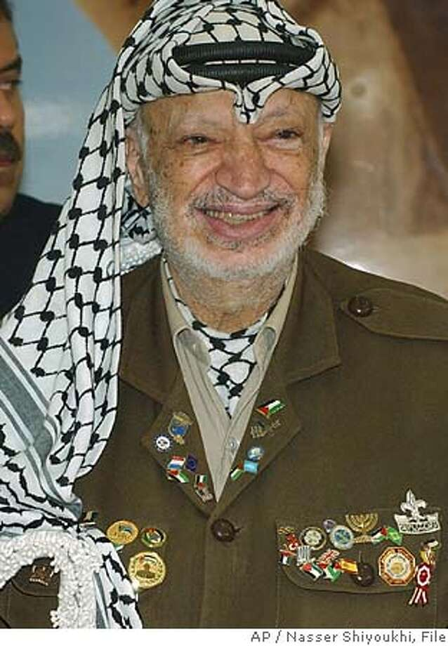 ** FILE ** Palestinian leader Yasser Arafat smiles during a gathering with supporters at his headquarters in the West Bank town of Ramallah, in this Tuesday Aug. 3, 2004 photo. Yasser Arafat's medical records do not give conclusive results as to what caused his death, The New York Times and the Haaretz newspapers reported Thursday. A stroke was the final blow that killed Arafat, but it is not clear what led to a deterioration in his health, The New York Times concluded in its report. The records show that Arafat's symptoms make it highly unlikely that he died of AIDS or poisoning, the newspaper said. Arafat died in a Paris hospital Nov. 11 at the age of 75. He had fallen ill in mid-October, and doctors originally said he had the flu. (AP Photo/Nasser Shiyoukhi) Photo: NASSER SHIYOUKHI