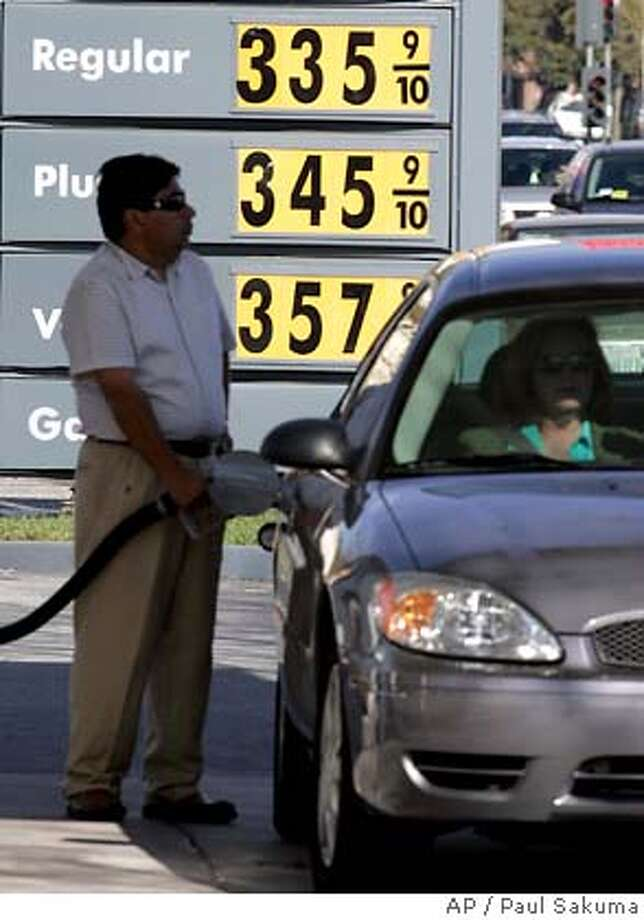 A Shell gas station customer pumps gas with high gas prices posted in background in Palo Alto, Calif., Monday, March 12, 2007. (AP Photo/Paul Sakuma) Photo: PAUL SAKUMA