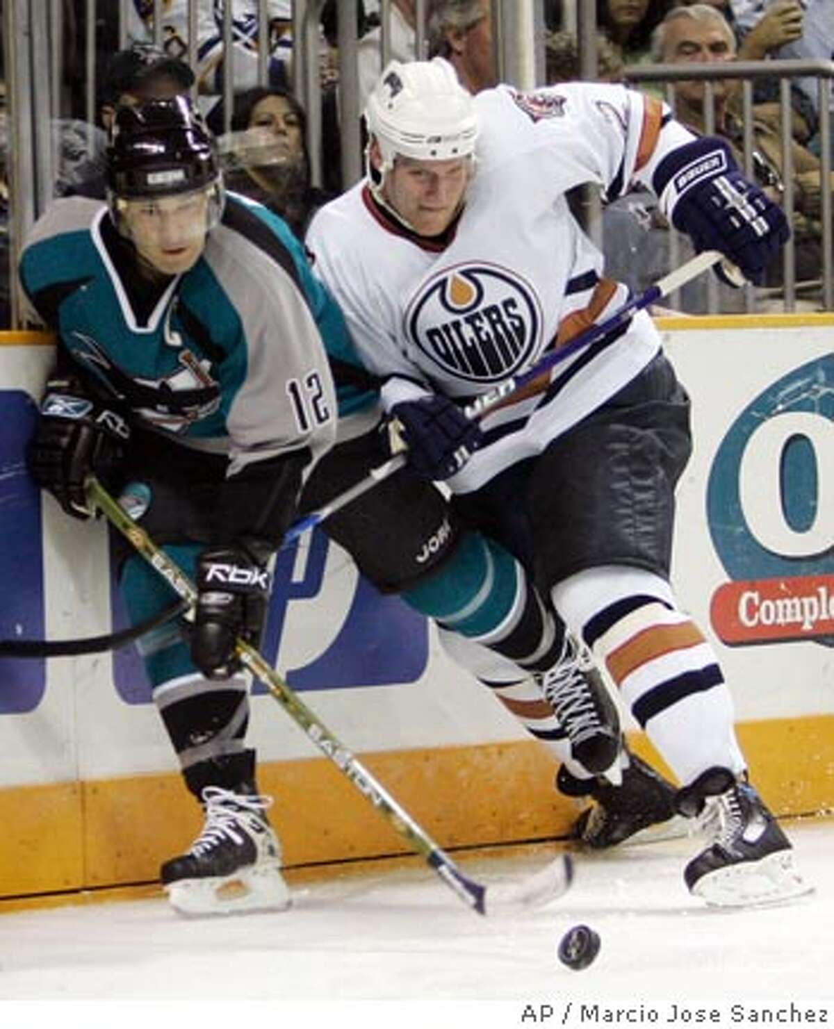 San Jose Sharks center Patrick Marleau, left, battles with Edmonton Oilers defenseman Matt Greene in the second period of an NHL hockey game in San Jose, Calif., Sunday, March 11, 2007.(AP Photo/Marcio Jose Sanchez)