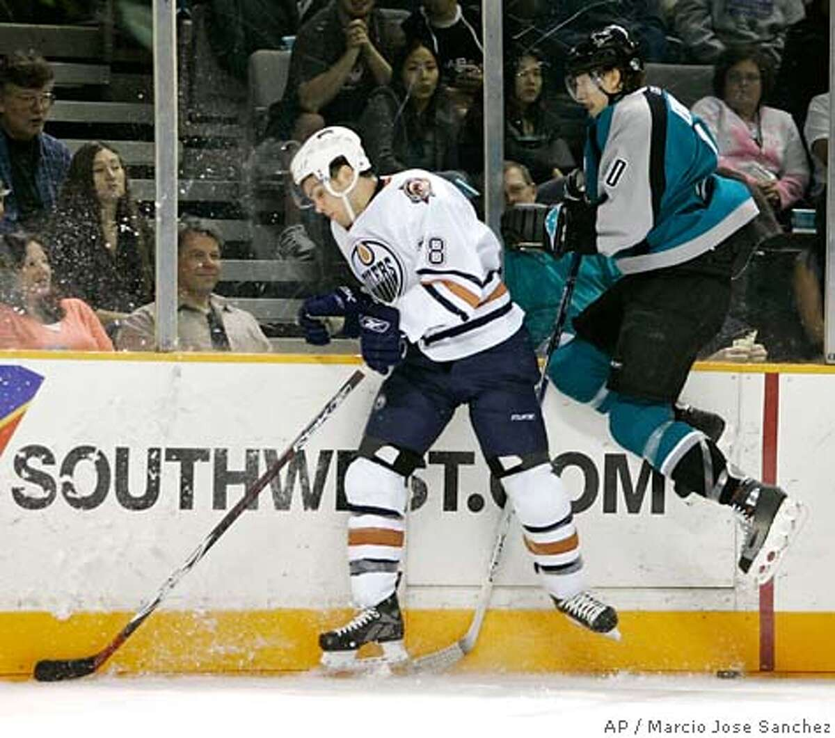 Edmonton Oilers center Marc-Antoine Pouliot, left, collides with San Jose Sharks defenseman Christian Ehrhoff, of Germany, in the first period of an NHL hockey game in San Jose, Calif., Sunday, March 11, 2007.(AP Photo/Marcio Jose Sanchez)