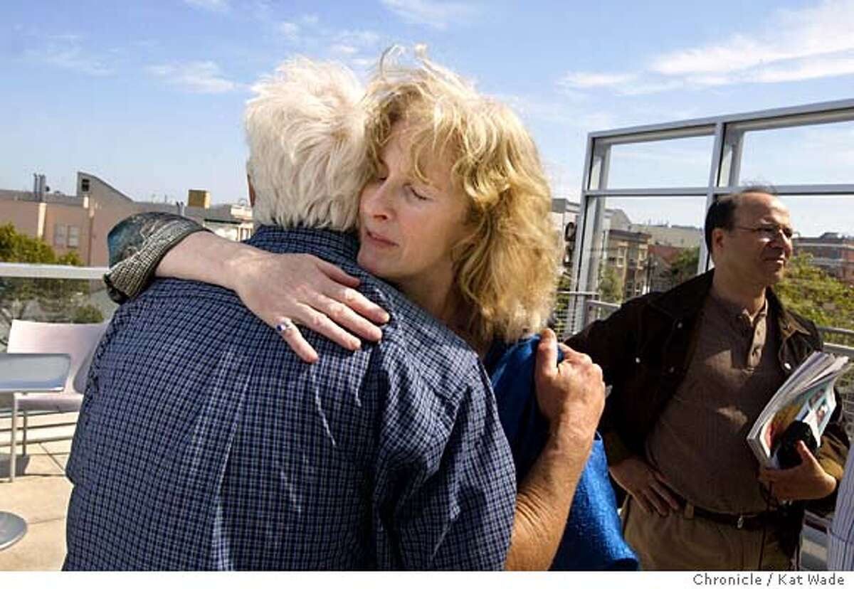 Longtime Lesbian activist, Phyllis Burke(center) gets a hug from Dennis Peron, a friend of Harvey Milk's and the author of the 215, the medical marijuana bill, after her dramatic reading she wrote with a grant from the San Francisco Art Commission titled,