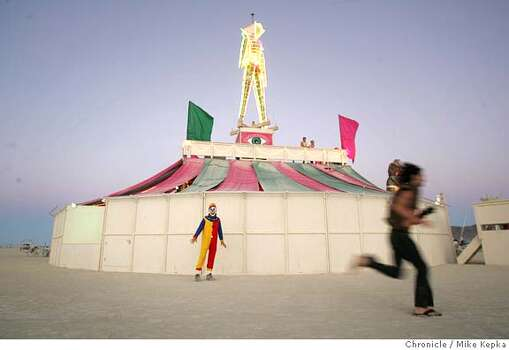 "Bob Dye of Seattle hovers around the Man at dusk during Burning Man 2005. ""I'm like a release for a bad evil dream,"" he said wearing a scary clown mask.  Photo: Mike Kepka"