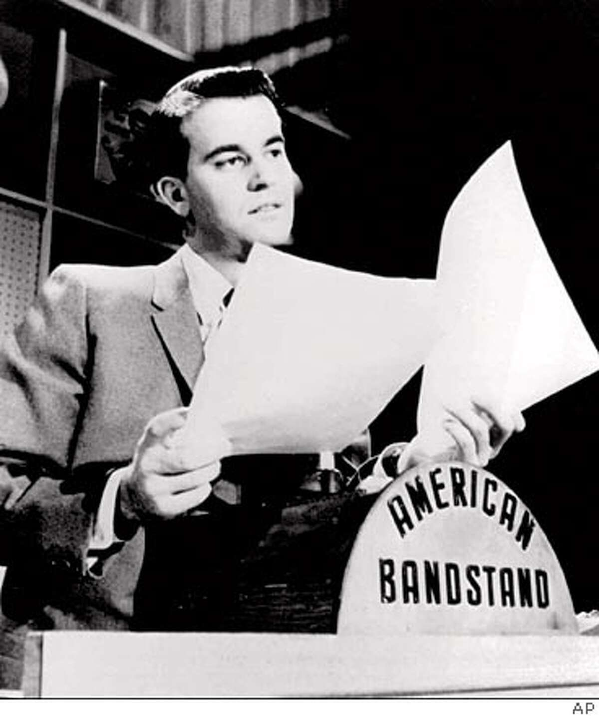 """ADV. FOR WKD. EDS., NOV. 4-7--FILE--Dick Clark looks over some papers during an """"American Bandstand"""" show in Philadelphia in this undated photo. """"American Bandstand"""" first aired as a local show in Philadelphia, gained popularity with host Dick Clark after he joined the program in 1956, and then went national in 1957. (AP Photo/File) ALSO RAN 5/2/02"""