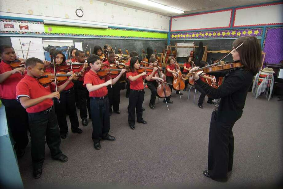 Fifth-grade members of the Suzuki Ensemble at Parker Elementary School practice with violin teacher Elizabeth Benne as they prepare to perform at the Suzuki Association of America's 40th anniversary convention in Minneapolis. Photo: R. Clayton McKee / © R. Clayton McKee