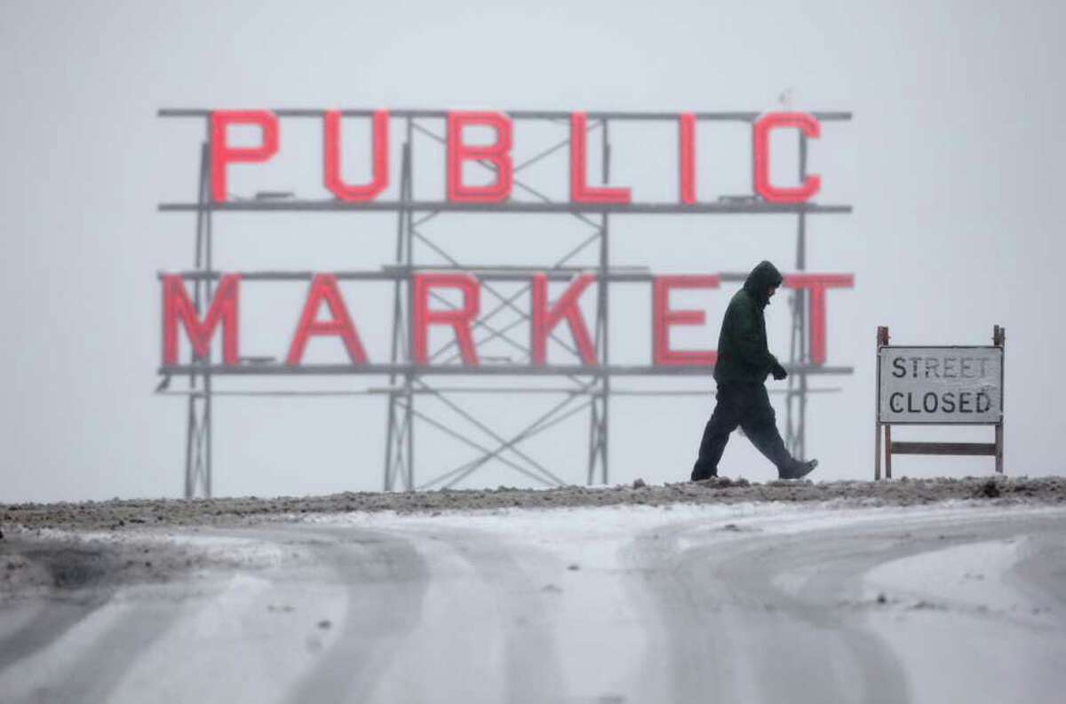 A pedestrian crosses Pine Street near the landmark Pike Place Market on Wednesday, January 18, 2012 in Seattle. Heavy snow fell in the city, wreaking havoc with area roads and transit, and closing many businesses and schools.