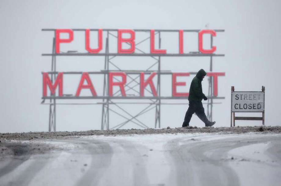 A pedestrian crosses Pine Street near the landmark Pike Place Market on Wednesday, January 18, 2012 in Seattle. Heavy snow fell in the city, wreaking havoc with area roads and transit, and closing many businesses and schools. Photo: JOSHUA TRUJILLO / SEATTLEPI.COM