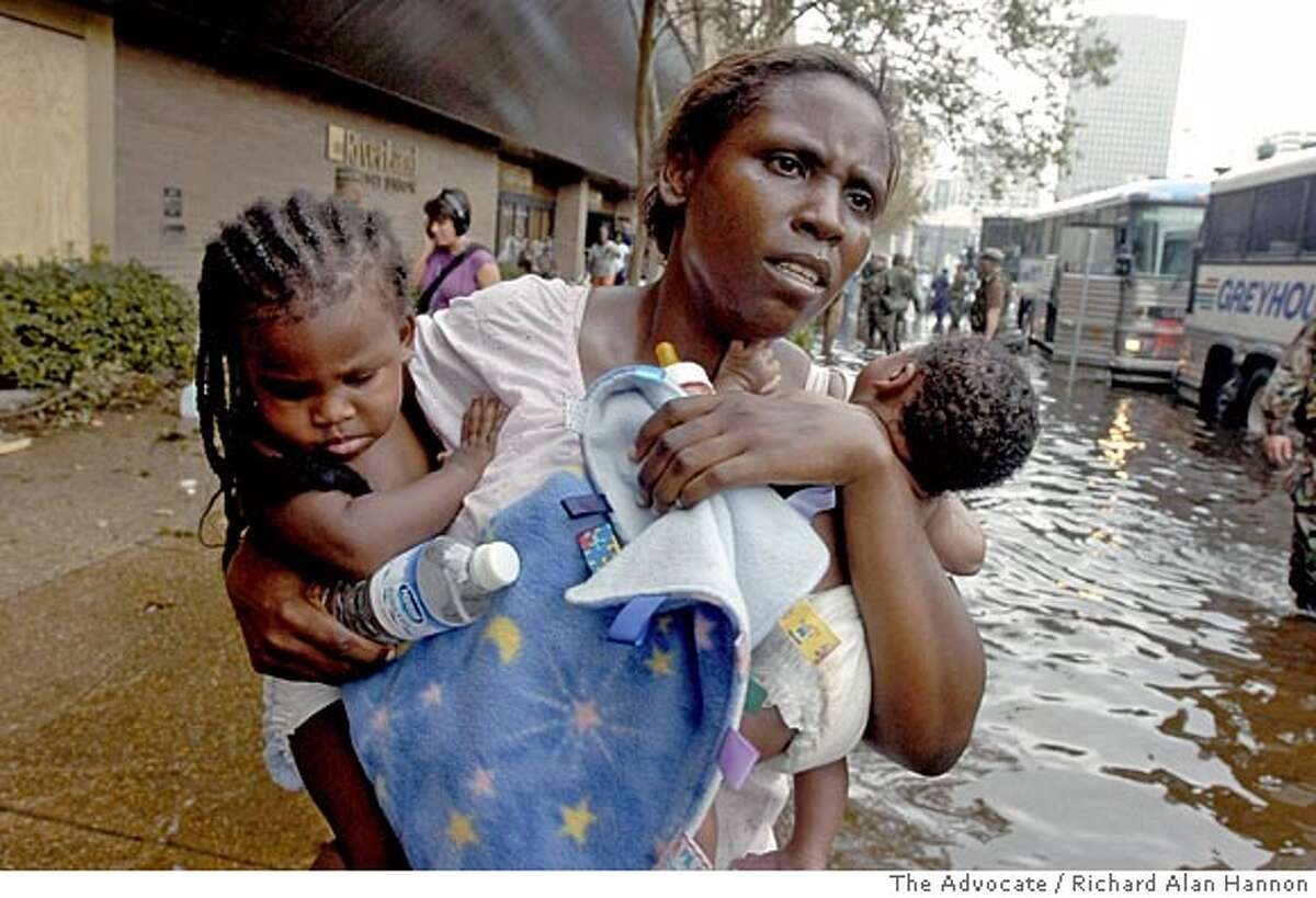 ** RETRANSMITTING FOR IMPROVED QUALITY ** A Hurricane Katrina refugee and her two babies wade through the water out to a waiting chartered bus outside the Hyatt Regency Hotel in New Orleans, Thursday, Sept.1, 2005. Starting with an estimated 16,000-20,000 people and estimated to continue through the night, refugees were walked through the lower level of the hotel to the awaiting air-conditioned buses. (AP Photo/The Advocate, Richard Alan Hannon) , MAGS OUT, INTERNET OUT