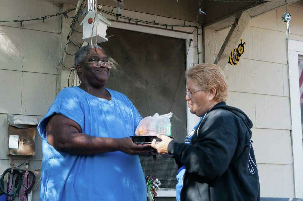 Margaret M. Gaines accepts a meal package from volunteer Concepcion Herrera that was brought through a Meals on Wheels program operated by Interfaith Ministries of Houston.