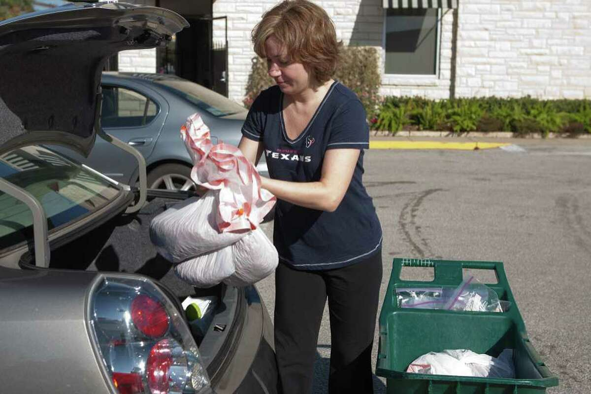 Volunteer Danielle Devine loads pet food into her trunk for delivery to her senior clients as part of the Meals On Wheels program run by Interfaith Ministries of Houston. Photo by R. Clayton McKee